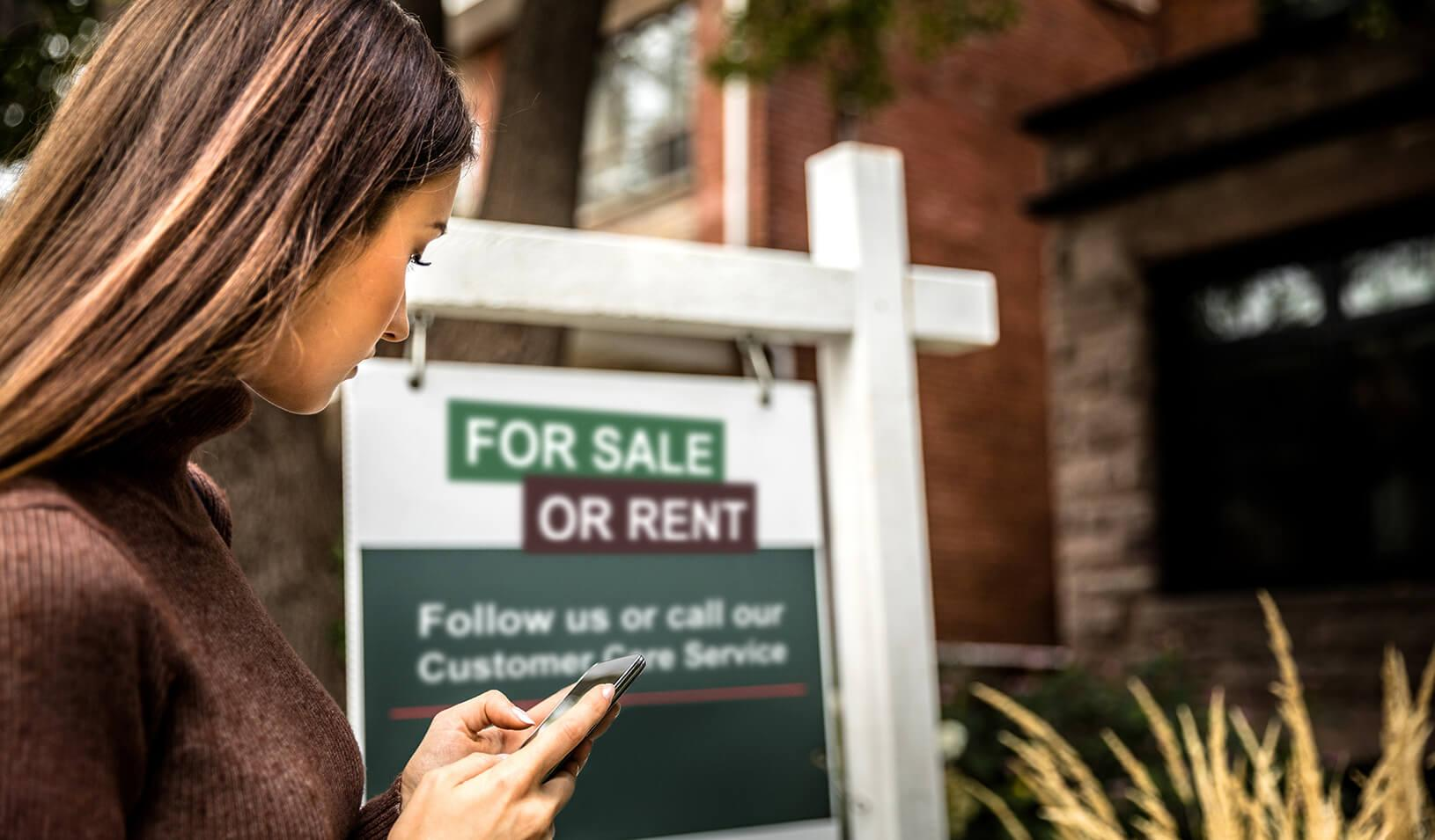 A woman taking a photo of a for-sale sign in front of a house. Credit: iStock/Leonardo Patrizi