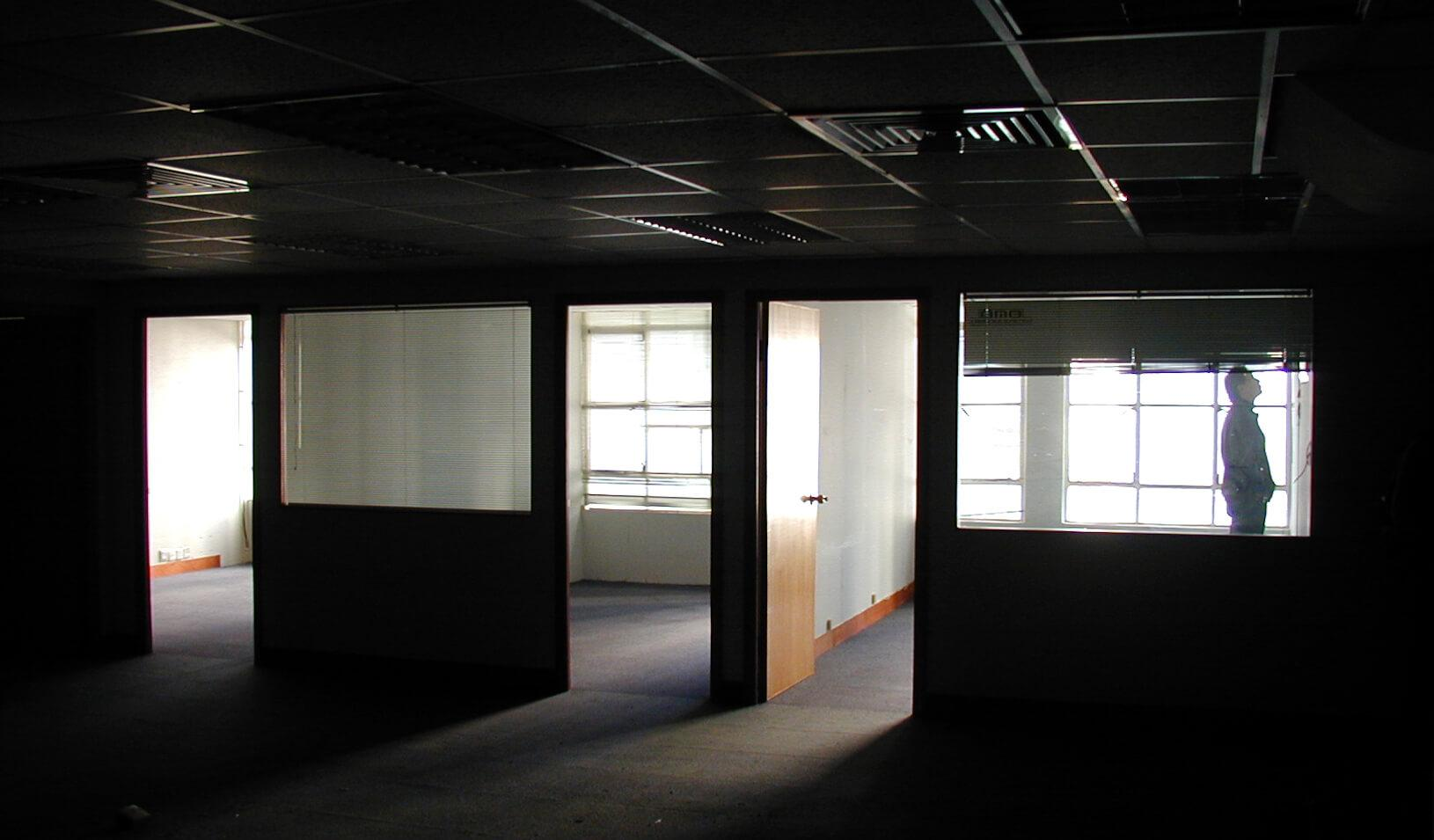Man stands alone in dark abandoned office building. Credit: istock/blackred