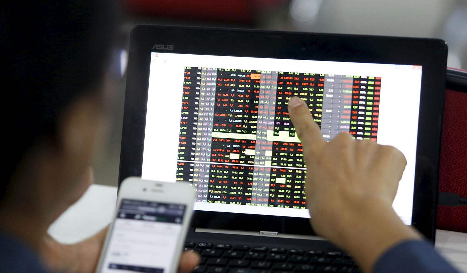 user pointing at computer screen showing stock prices