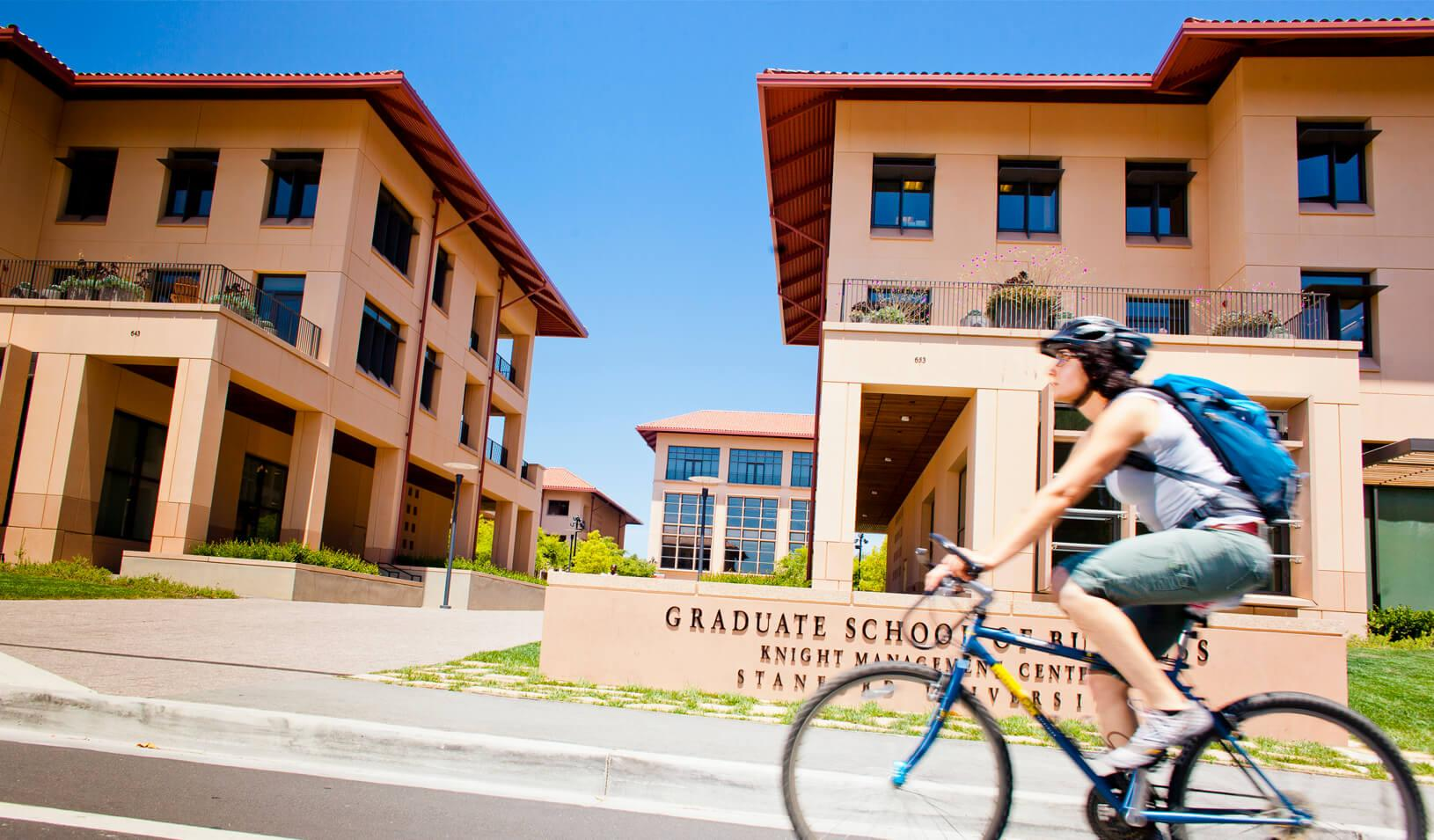 A woman rides her bike past the Knight Management Center. Credit: Elena Zhukova