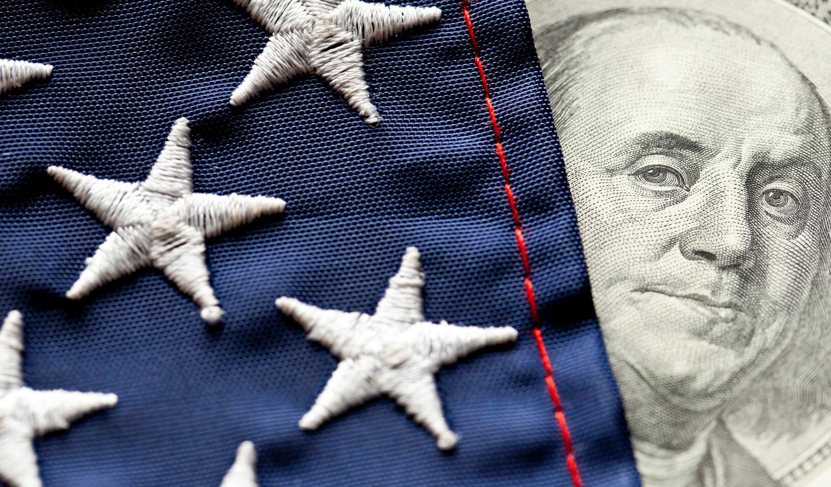 A photo illustration of the face of George Washington on the dollar bill peeking out from behind the U.S. Flag. Credit: iStock/Bill Oxford