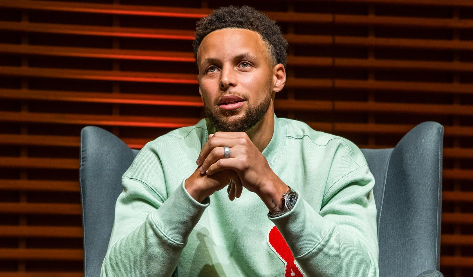 Close up shot of Wardell Stephen Curry sitting and holding his hands, looking off camera. Credit: Stacy Geiken