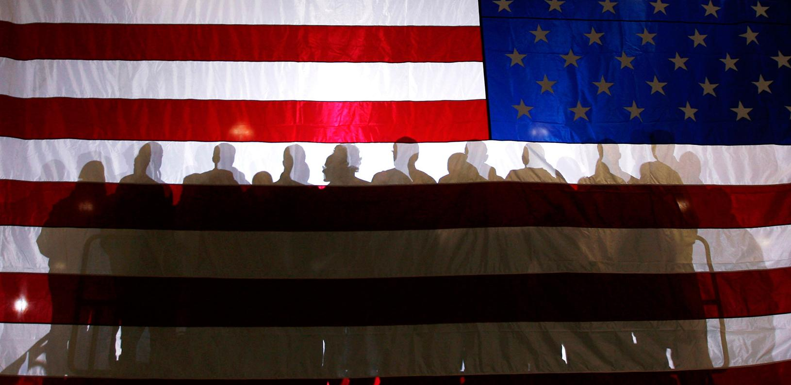 Shadows of a group of people against an American flag backdrop
