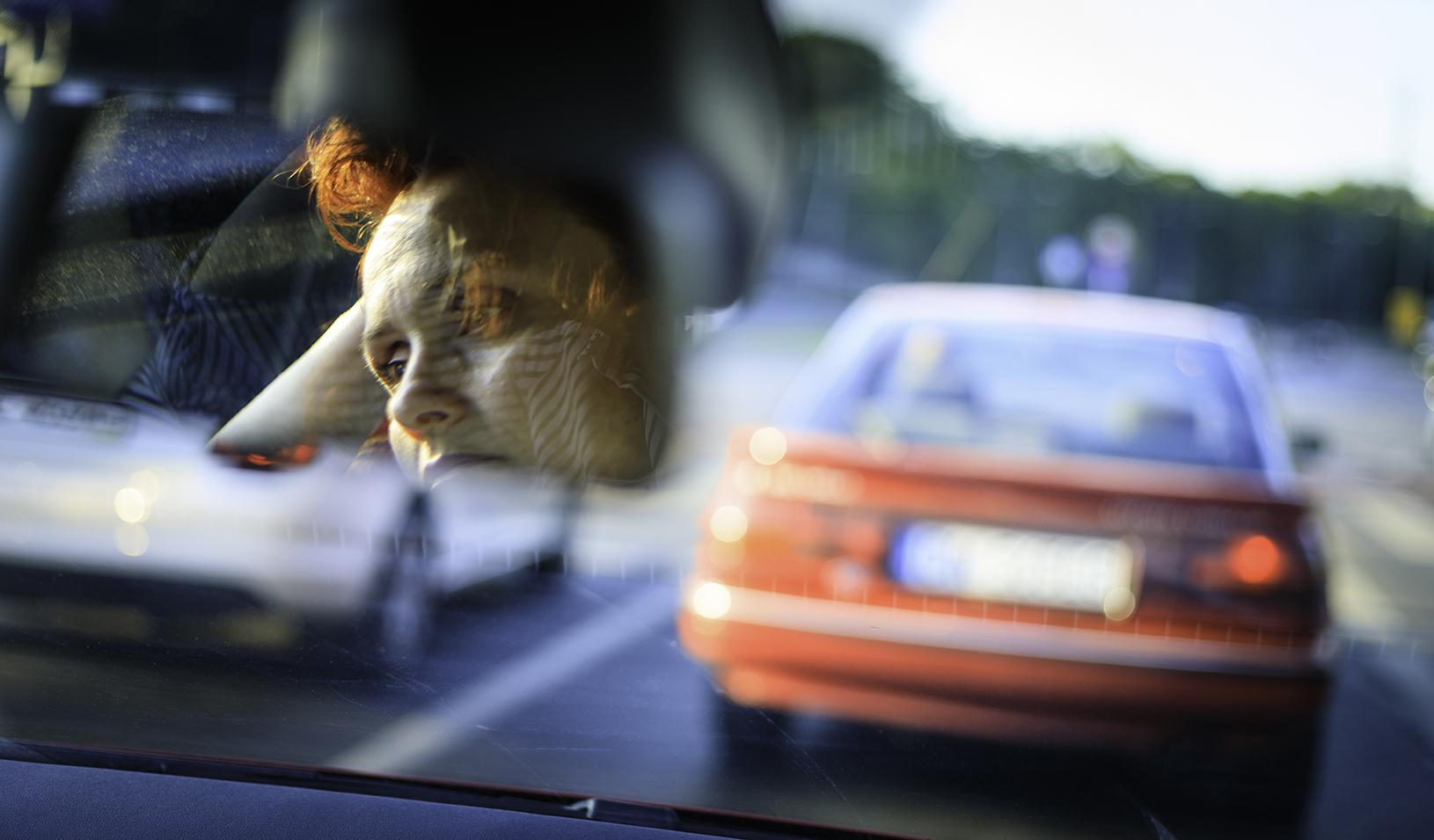 Woman driving in traffic, looking stressed through her rearview mirror. Credit: iStock/Republica