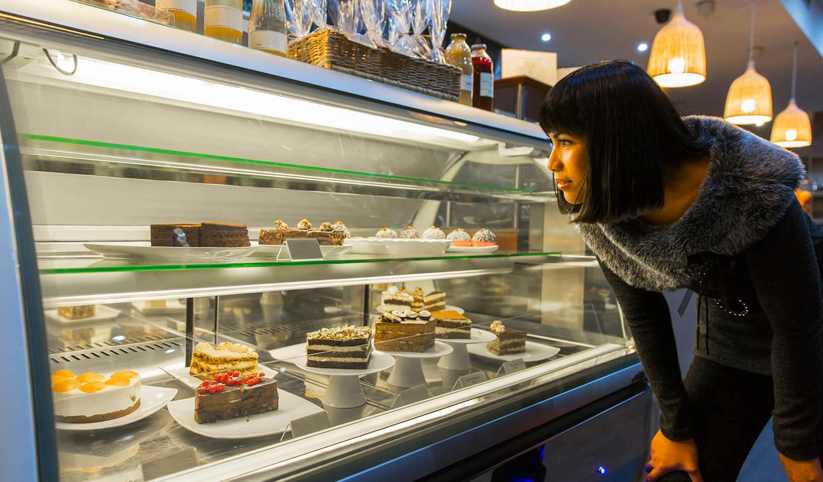 A woman looks at a case of desserts