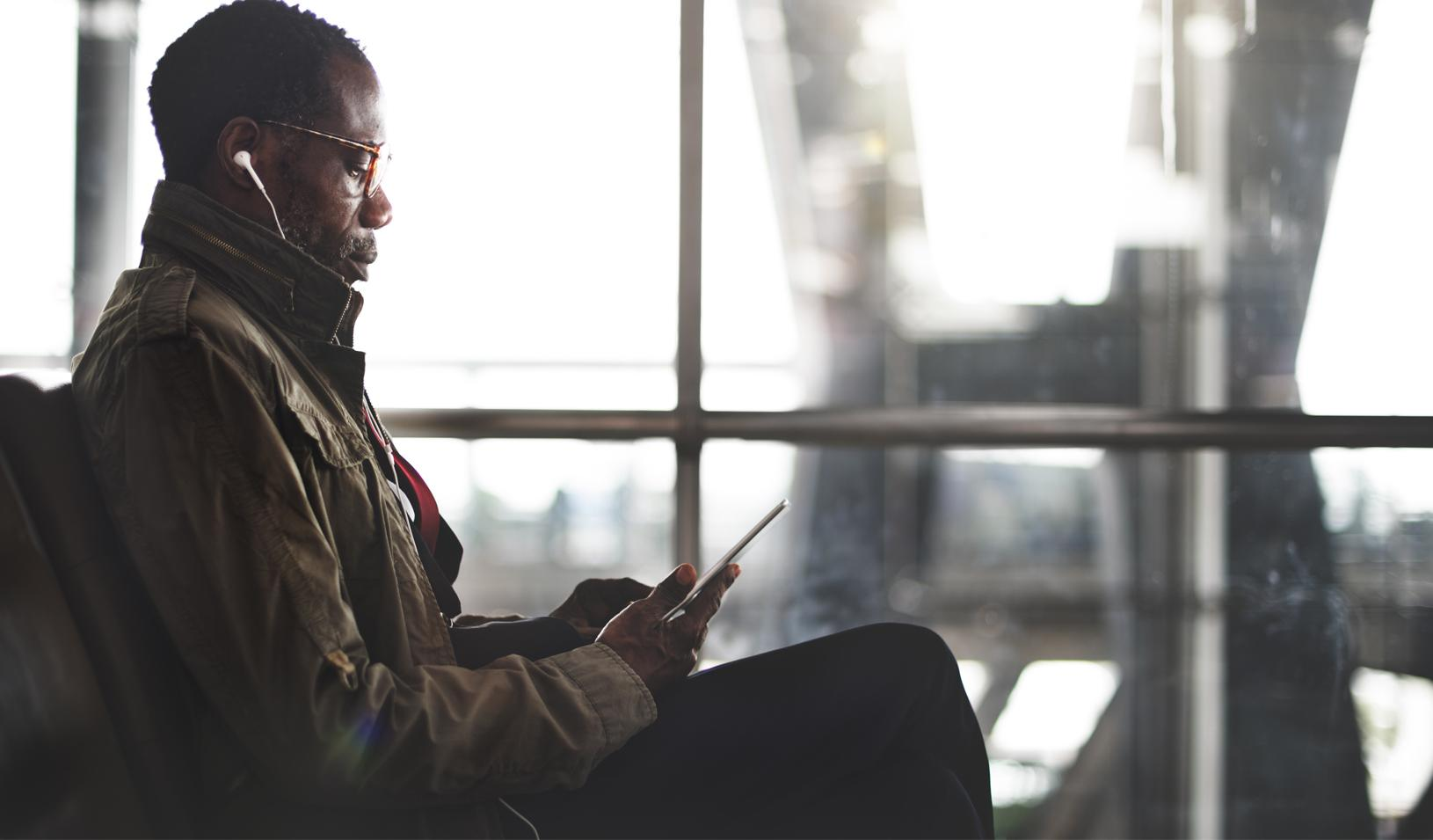 An African American businessman watching videos on his tablet at the airport. Credit: iStock/rawpixel