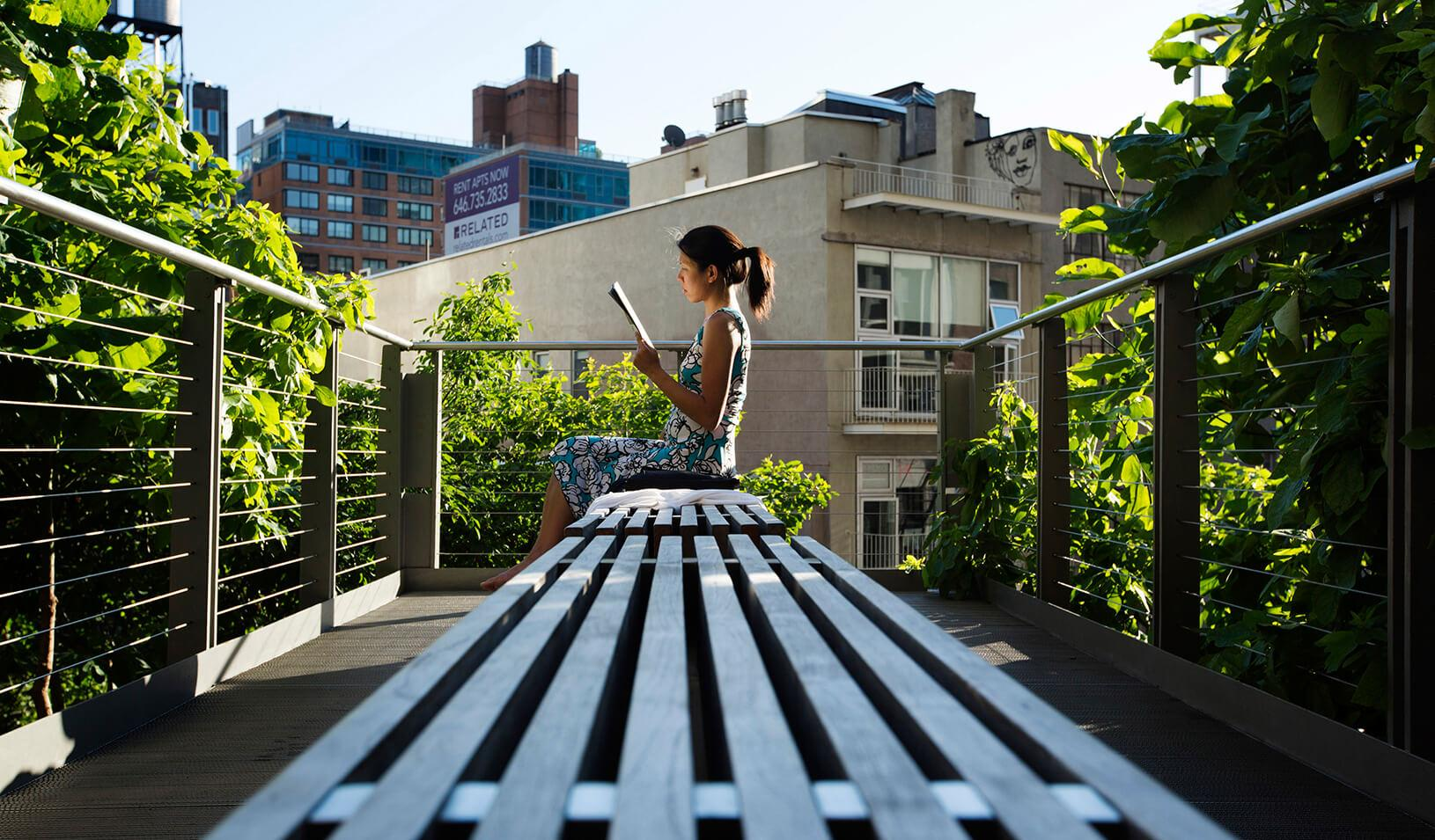 A woman uses the late afternoon sun to read while sitting on the High Line park in New York