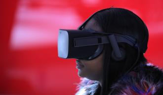 A woman wears VR goggles as she sits in a virtual reality booth. Credit: Reuters/Brendan McDermid