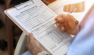 Health insurance claim form application for patient with illness in hospital ward. Credit: iStock/Chinnapong
