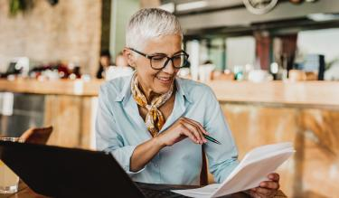 An older woman is sitting in a coffee shop and using laptop. Credit: iStock/blackCAT