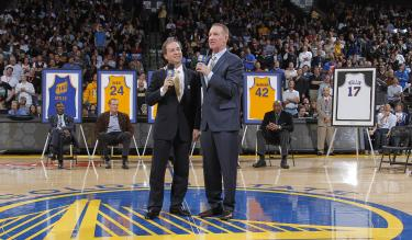 Golden State Warriors owner Joe Lacob, left, speaks with former player Chris Mullin during a ceremony to retire his #17 jersey at halftime of a game between the Warriors and Minnesota Timberwolves on March 19, 2012. Credit: Rocky Widner/NBAE via Getty Images