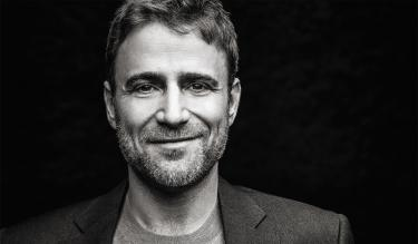 A dramatic black and white portrait of Stewart Butterfield smiling at the camera. Credit: Courtesy of Stewart Butterfield
