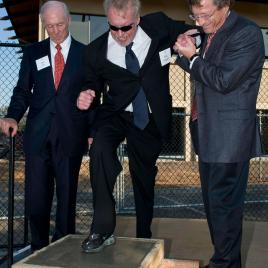 Dean Robert Joss (left) and Provost John Etchemendy (right), give Phil Knight, MBA '62, a hand putting his shoe print into concrete