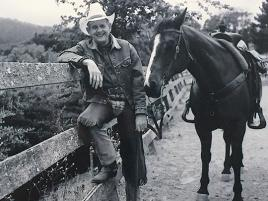 Bob Jaedicke standing by a fence with a horse next to him. Credit: Courtesy of Stanford GSB
