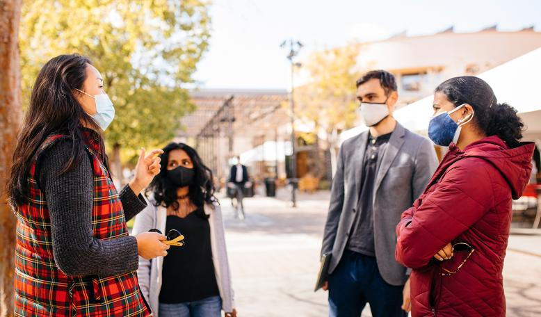 A group of masked students stop to talk in Town Square on campus. Credit: Elena Zhukova