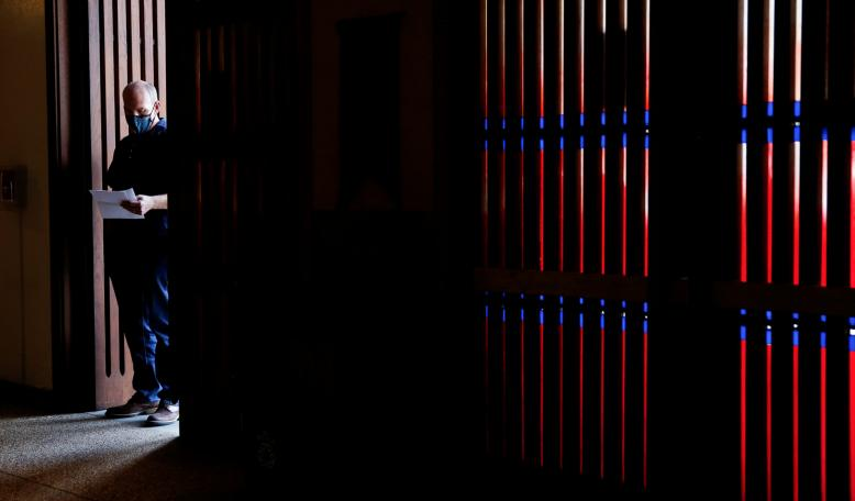 A patient waits in a doorway to check in for a COVID vaccination. Credit: Reuters/Lindsey Wasson