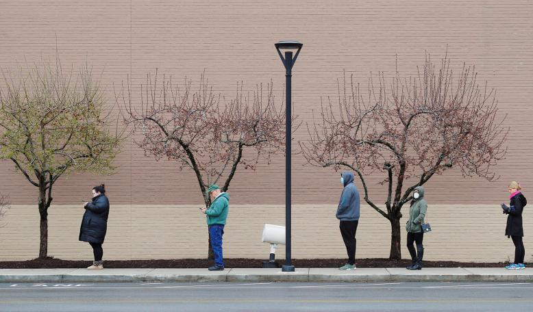 People line up at a safe social distance outside the grocery store amid the coronavirus disease (COVID-19) outbreak. Credit: Reuters/Brian Snyder