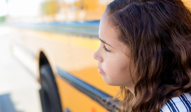 Mixed race schoolgirl daydreams while standing in front of a school bus. Credit: iStock/SDI Productions