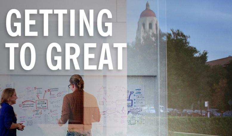 Two people write on a whiteboard with a reflection of Stanford University in the background. Credit: Elena Zhukova