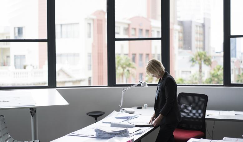An older woman standing at her desk. Credit: iStock/Portra