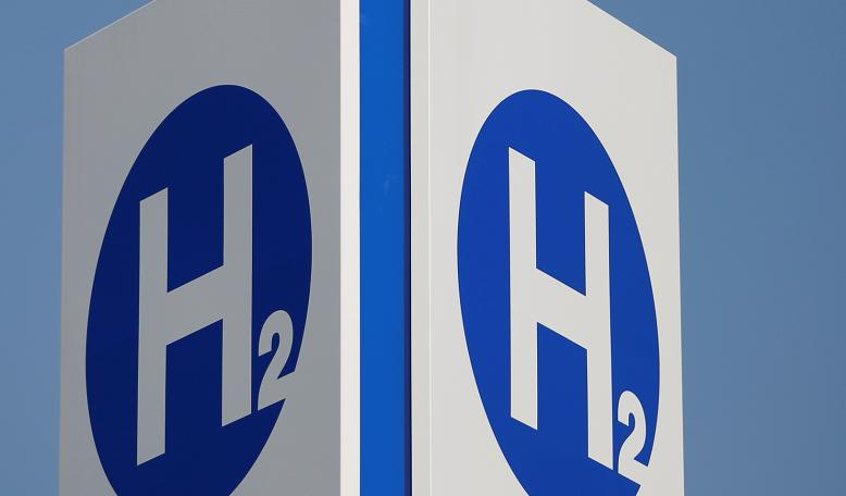 Hydrogen chemical symbols are displayed on a sign at a hydrogen station. Credit: Reuters/Issei Kato