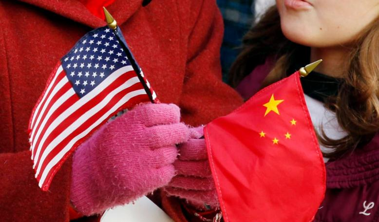 A girl holds a U.S. and Chinese flag. Credit: Reuters/Kevin Lamarque
