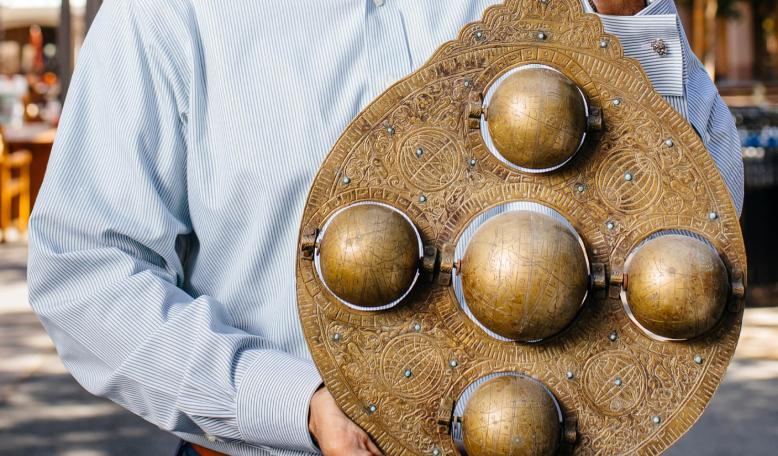 Saumitra Jha holds a brass astrolabe — a navigational tool used by medieval traders —that he bought while doing research in the port of Cochin, India.| Elena Zhukova