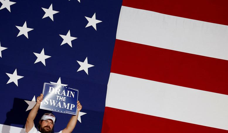 """A supporter of U.S. President Donald Trump holds a """"Drain the Swamp"""" sign. Credit: Reuters/Joshua Roberts"""