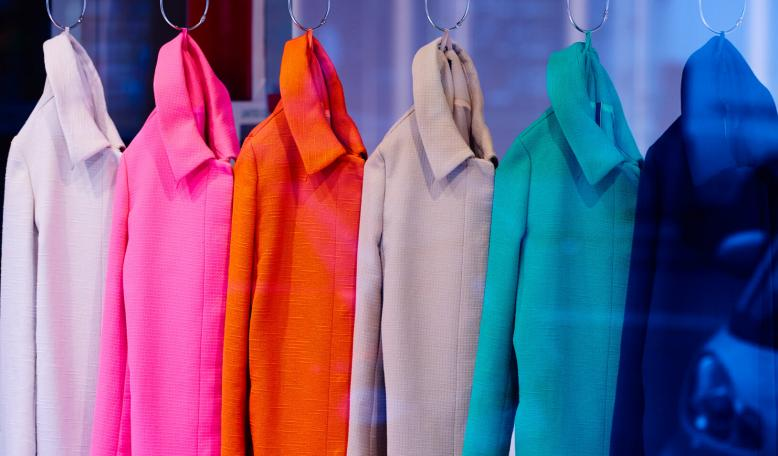 A rack of brightly colored coats. Credit: iStock/stock_colors