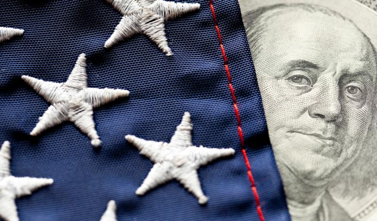 A photo illustration of the face of Benjamin Franklin on the hundred dollar bill peeking out from behind the U.S. Flag. Credit: iStock/Bill Oxford
