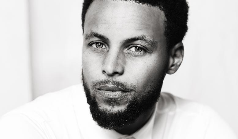 Black and white dramatic portrait of Stephen Curry smiling at the camera. Credit: Courtesy of Stephen Curry