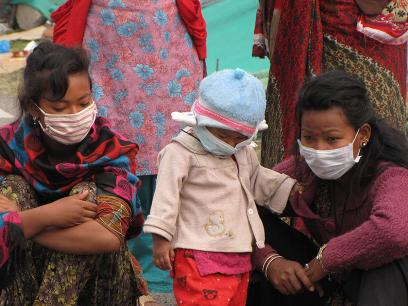 a little baby and two women with masks over their faces