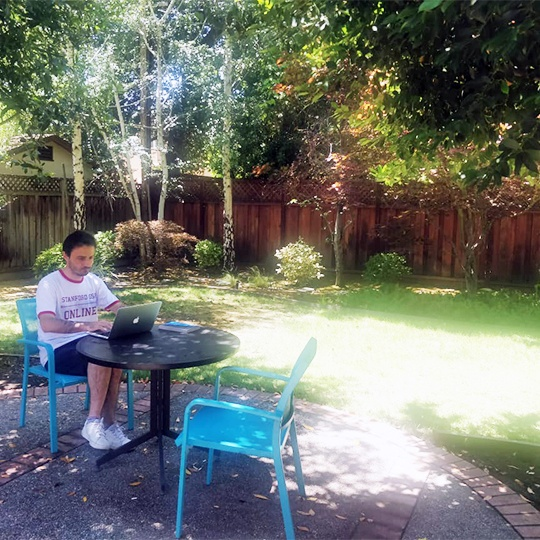 Sefa working at table in backyard