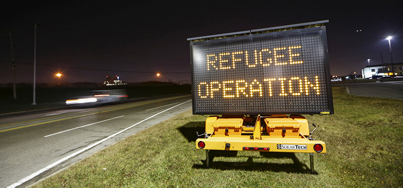 "A car drives by a sign on a road displaying ""Refugee Operation"""