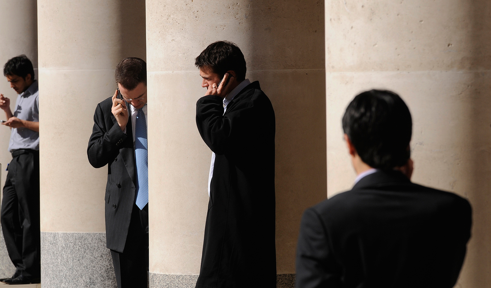 City workers make phone calls outside the London Stock Exchange