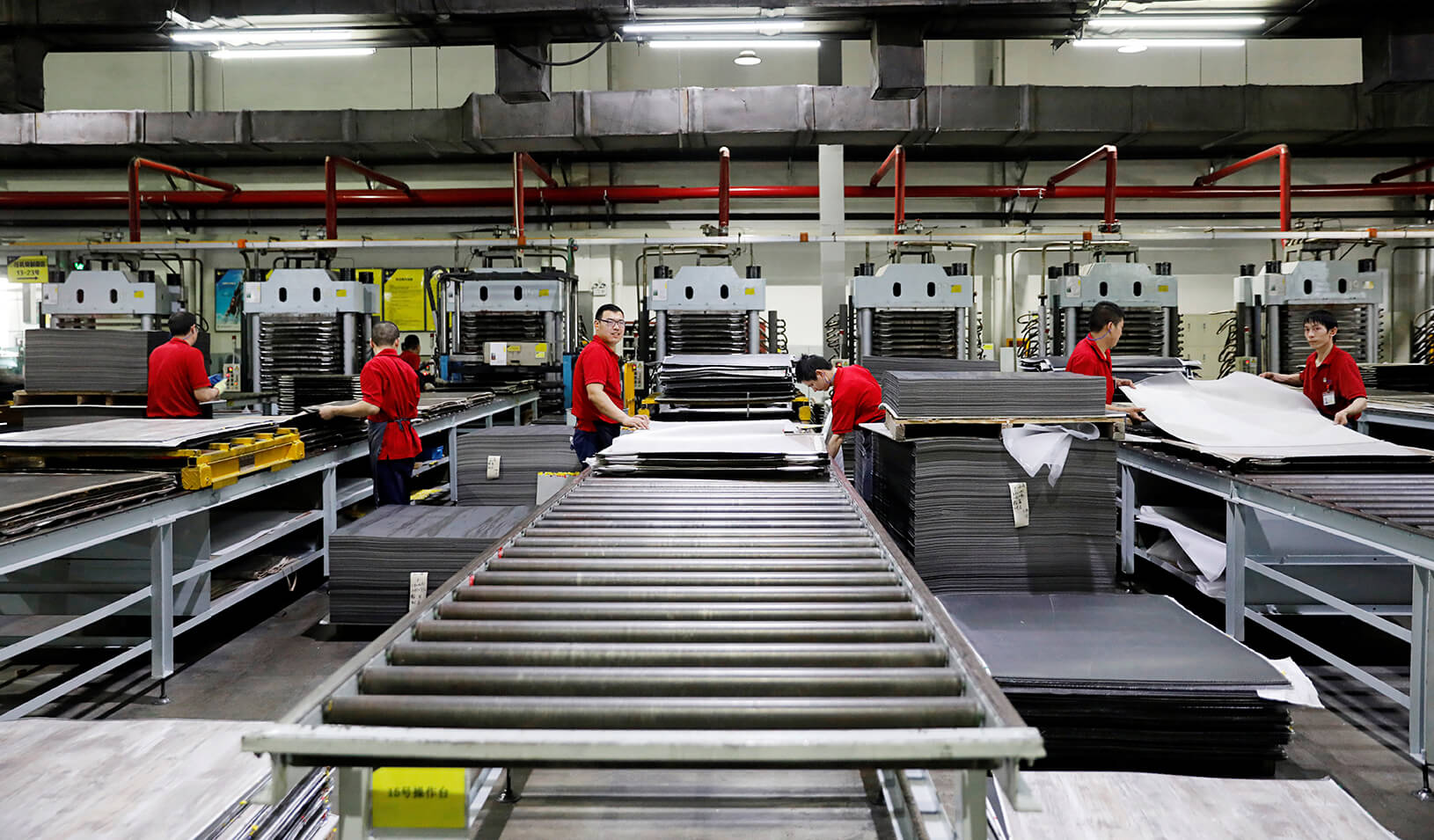 Employees work on a PVC plastic flooring production line. Credit: Reuters/Aly Song