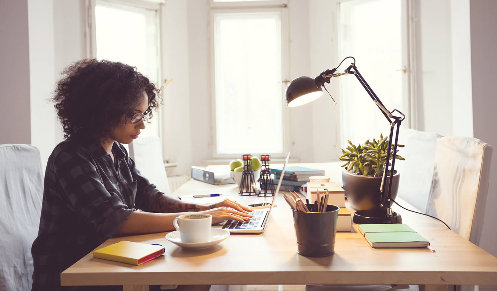 A young woman works at her home office. | iStock/Izabela Habur