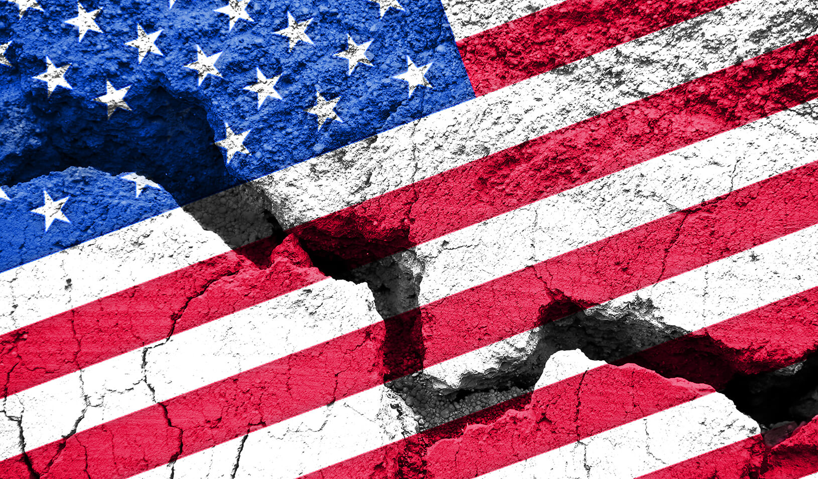 An american flag painted on cracked pavement | iStock/Delpixart