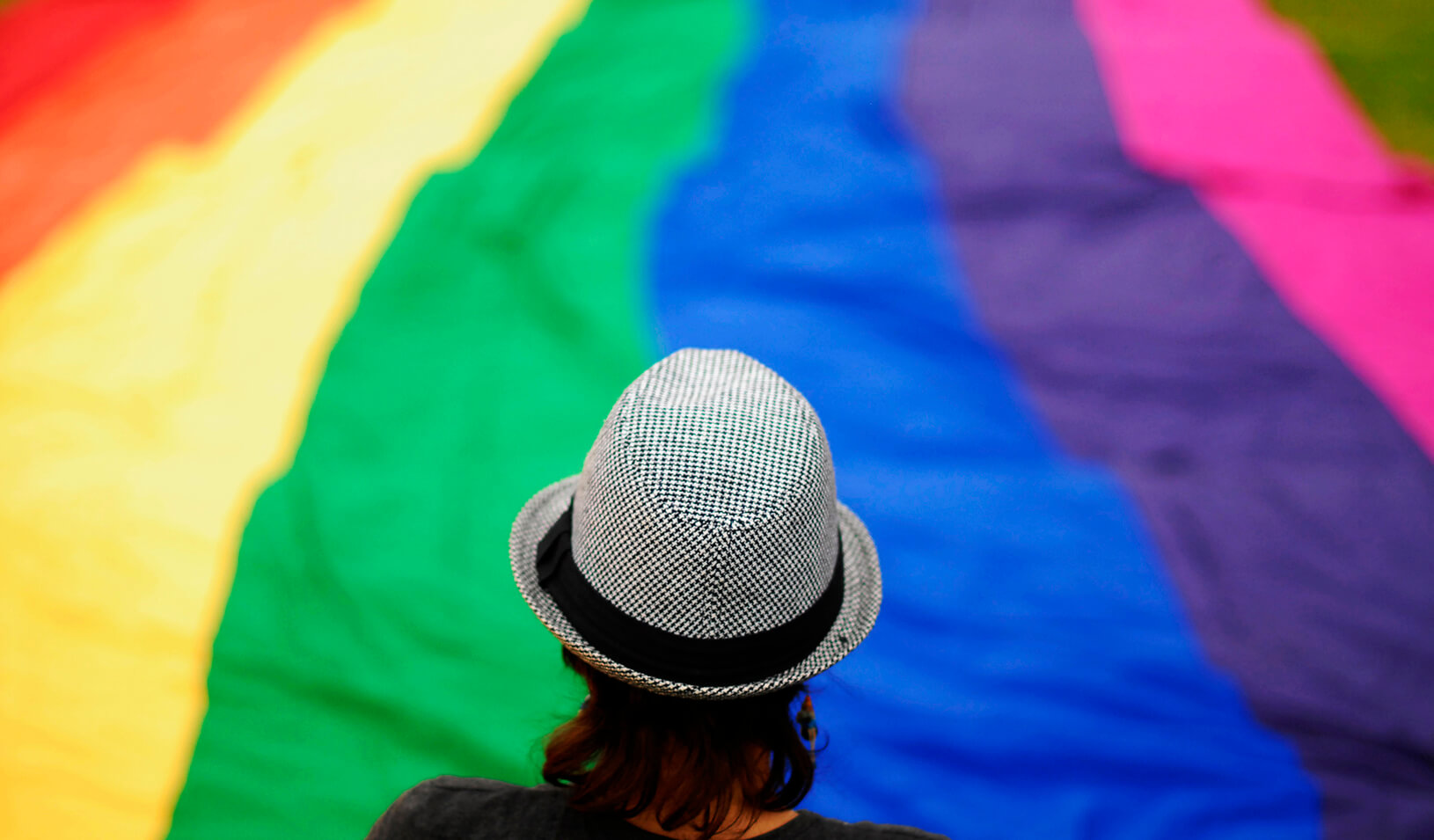 A transgender person overlooks a large rainbow banner  | Reuters/Ulises Rodriguez