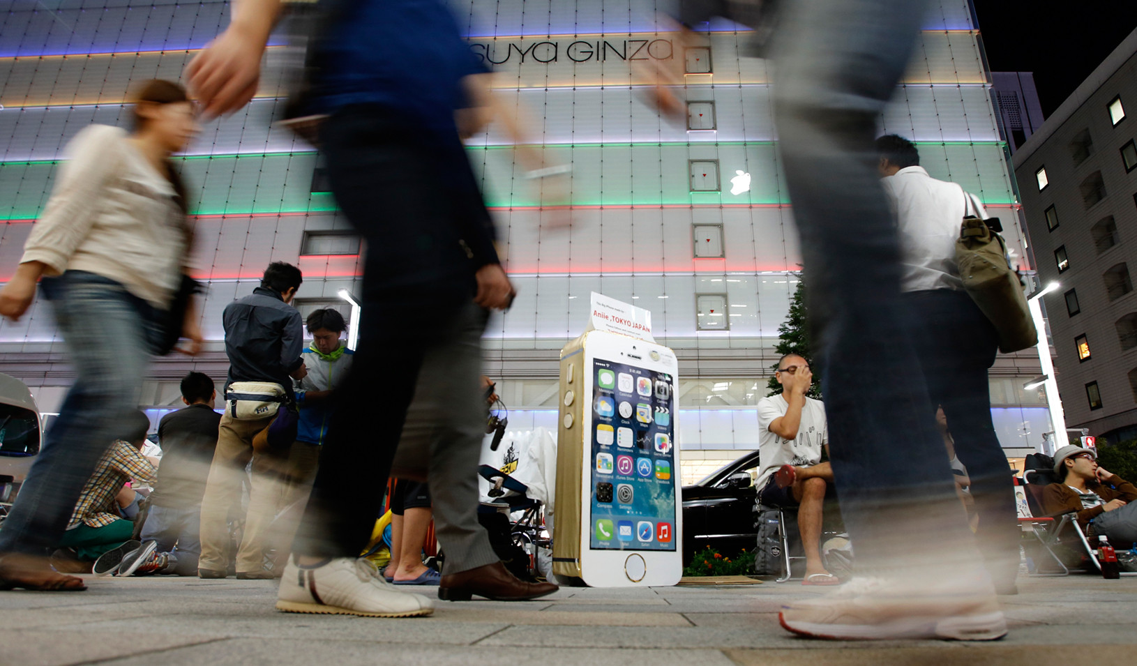 People sit next to a cardboard depicting Apple's new iPhone 5S in Tokyo, 2013 (Reuters photo by Toru Hanai)
