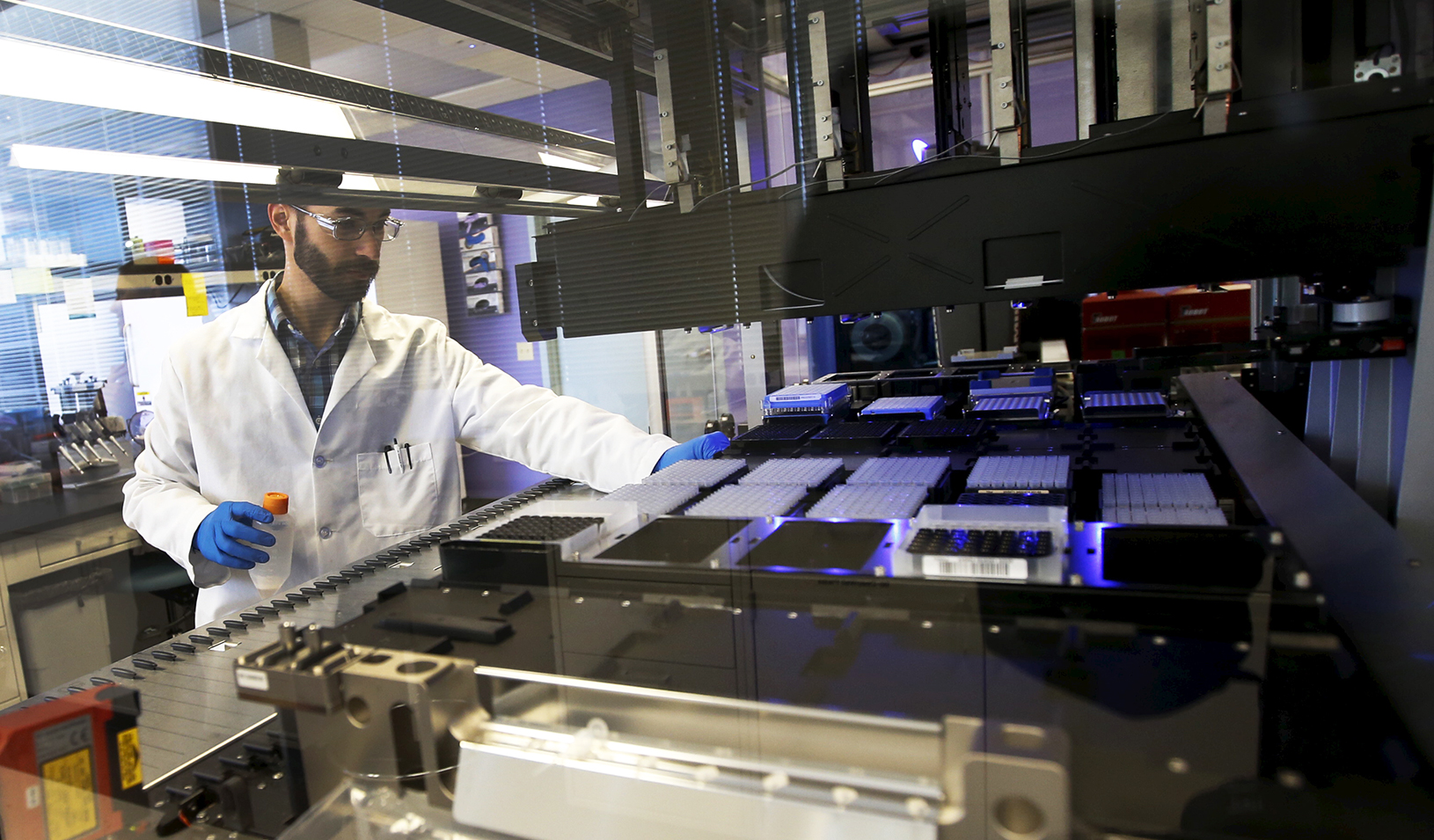 Technician loads a robotic DNA sample automation machine at a Regeneron Pharmaceuticals Inc. laboratory | Reuters/Mike Segar