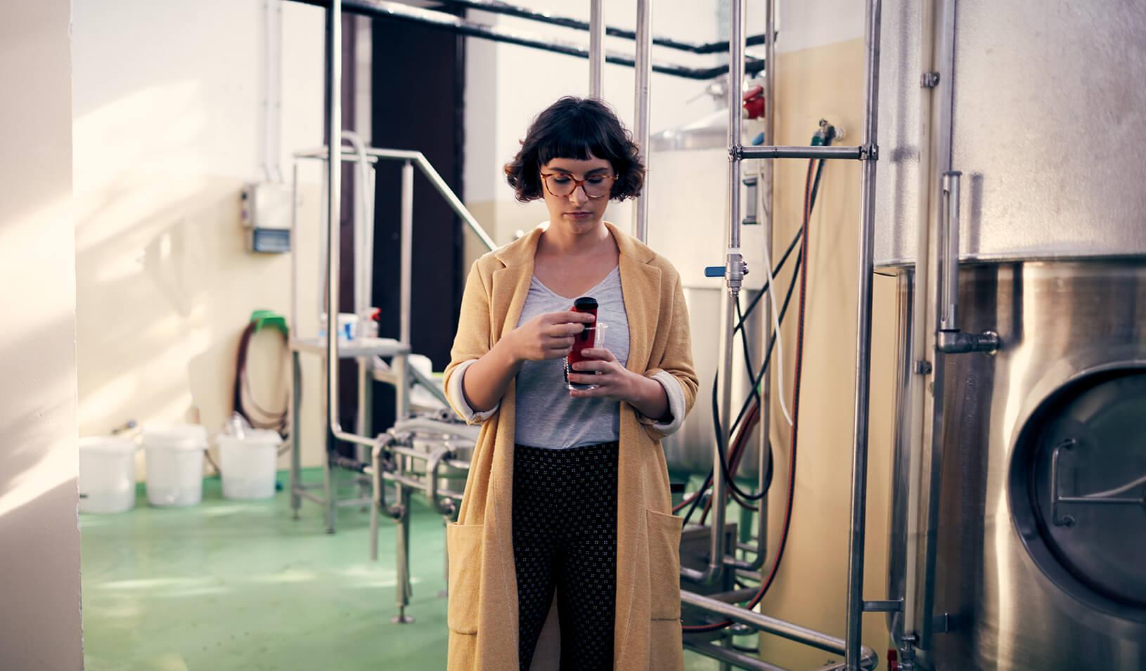 Woman craft beer maker examining her beer. Credit:iStock/vgajic