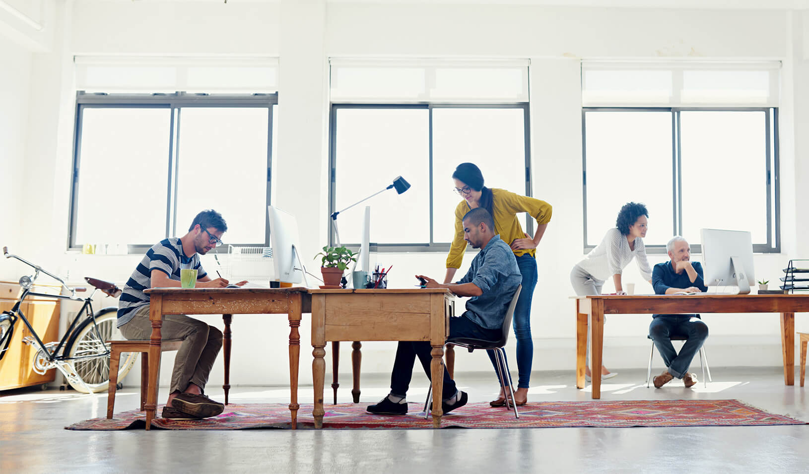 A diverse group of people working together​ | iStock/Yuri_Arcurs