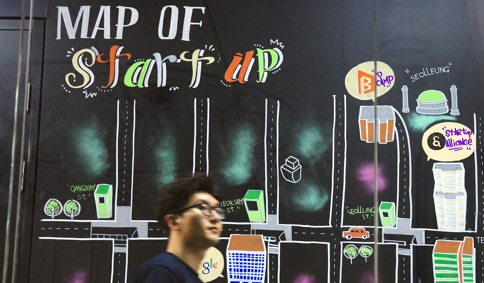 "Man walking past a wall painting labeled ""Map of Start-up"" at the Google Campus start-up space in the Gangnam district of Seoul. 