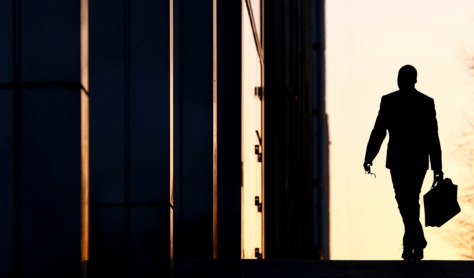 A businessman walking into the sunset with a briefcase. Credit: Reuters/Eddie Keogh