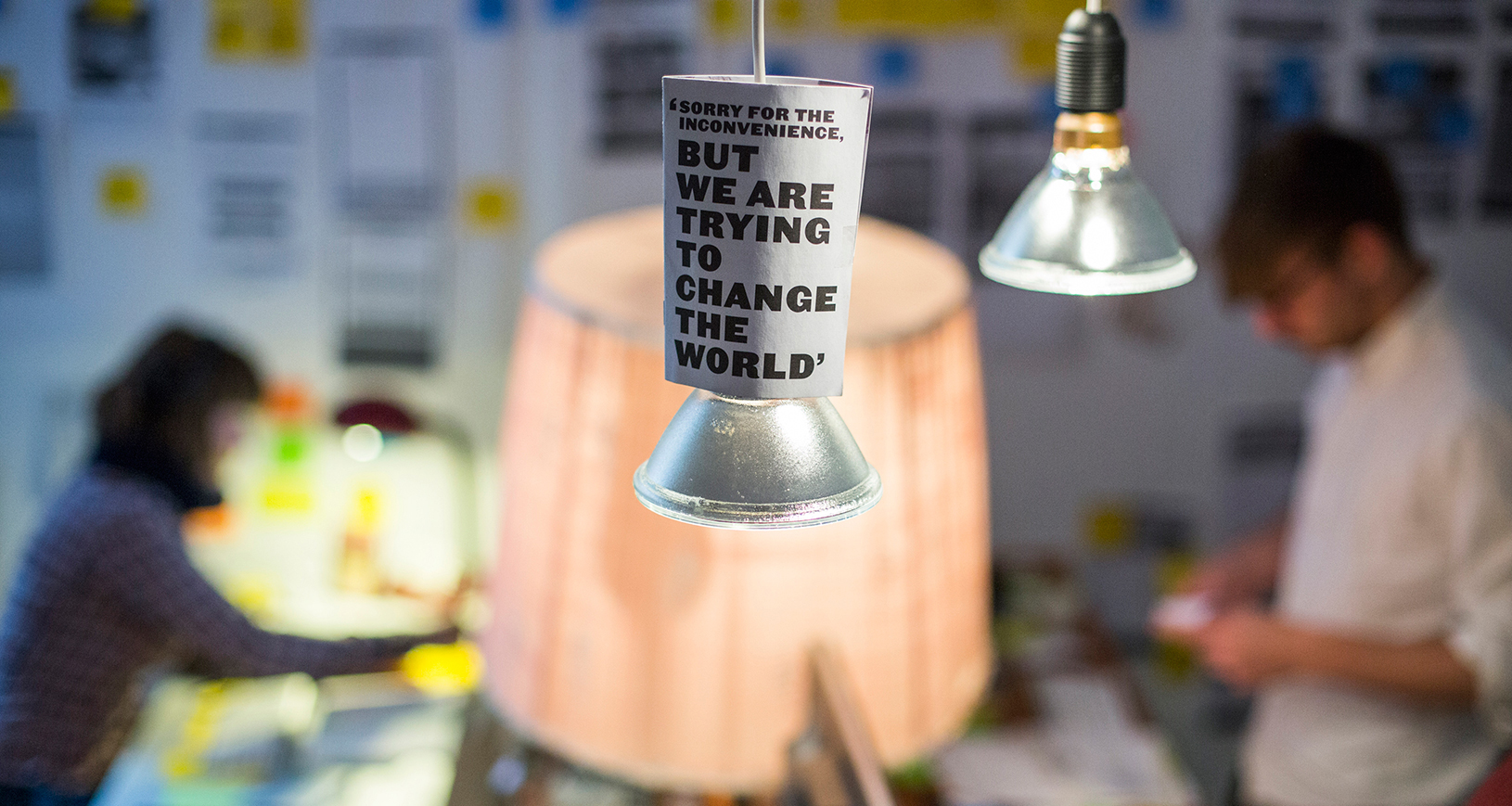 "A sign on a light in a startup office that reads, ""Sorry for the inconvenience, but we are trying to change the world."" Reuters/Thomas Peter"