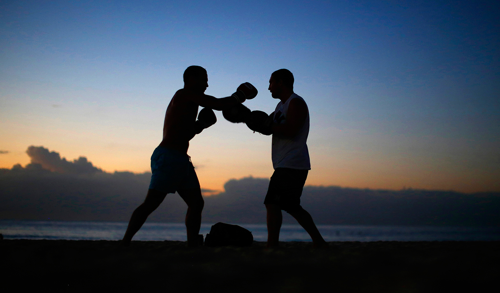 Two boxers sparing outside at dusk