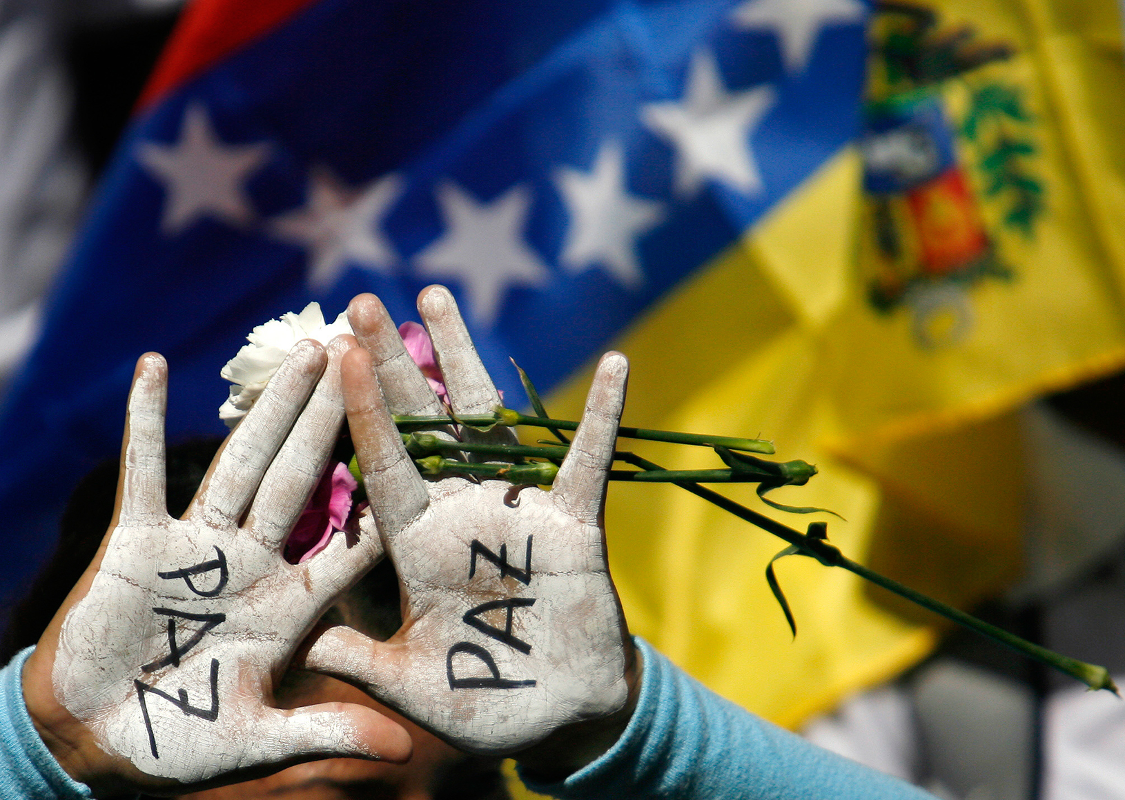 """""""Paz"""" - peace - painted on someone's hands"""