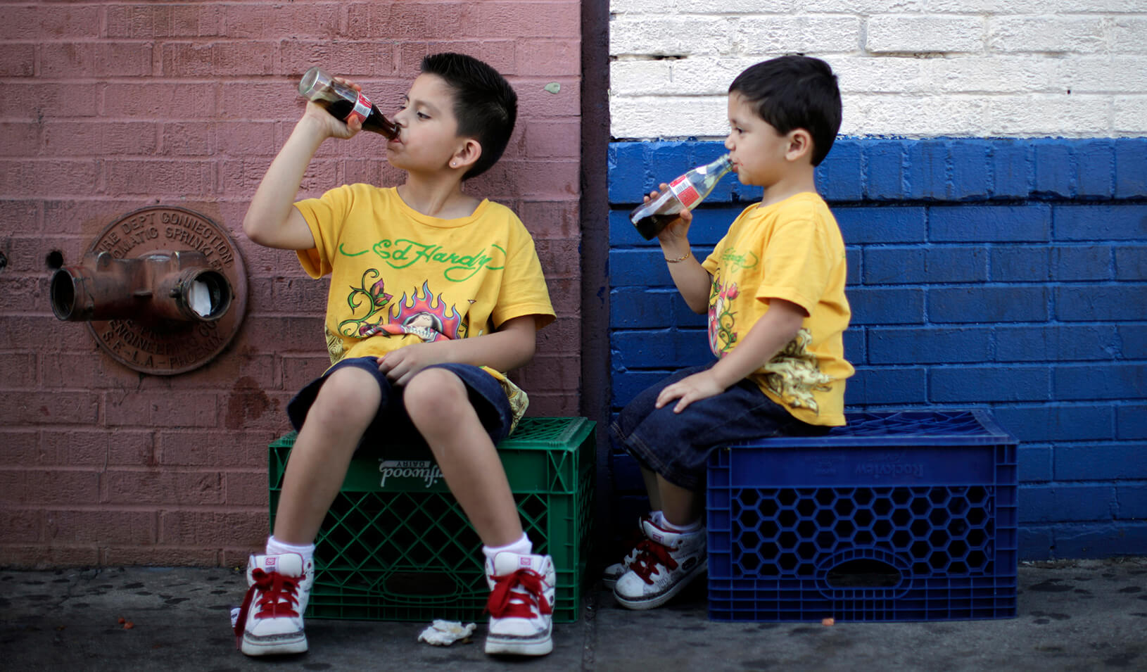 Children drink soda as they sit in the shade on a hot day. Credit: Reuters/Lucy Nicholson