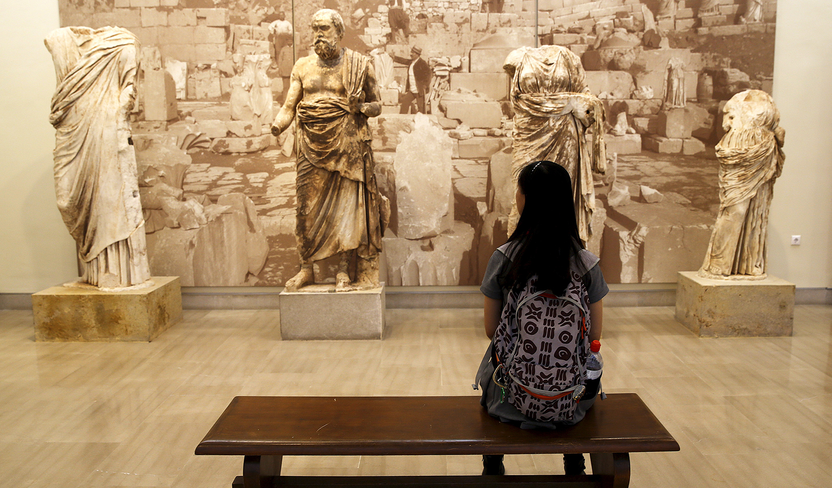 Woman sitting on a museum bench looking a sculptures | Reuters/Yannis Behrakis